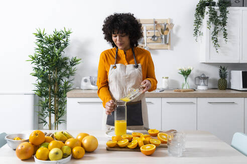 Woman pouring orange juice in bottle while standing at kitchen - GIOF10051