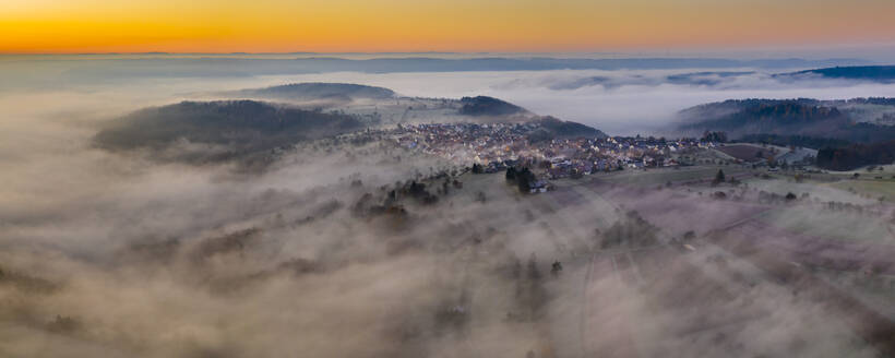 Germany, Baden-Wurttemberg, Berglen, Drone view of village shrouded in thick fog at dawn - STSF02737