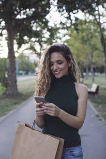 Smiling woman using smart phone in public park - MOMF00919