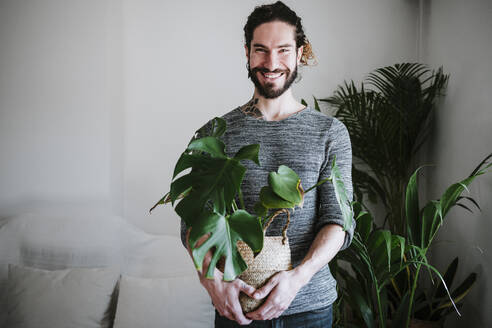 Young man smiling while holding Monstera plant at home - EBBF01819