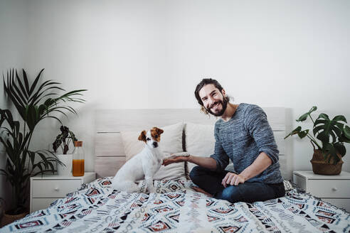 Handsome man playing with dog while sitting on bed at home - EBBF01843
