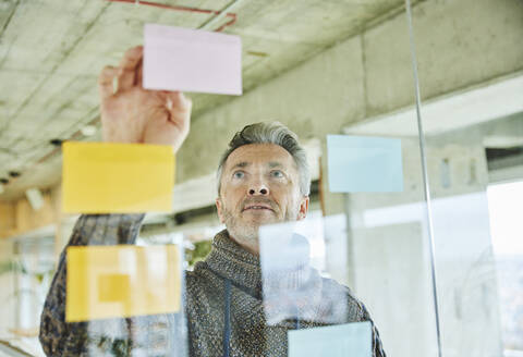 Male mature businessman putting note on glass wall while working at office - FMKF06879