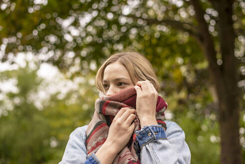 Young woman covering face with scarf in park - BFRF02330