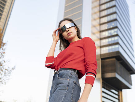 Woman wearing sunglasses standing against building in city - JCCMF00225