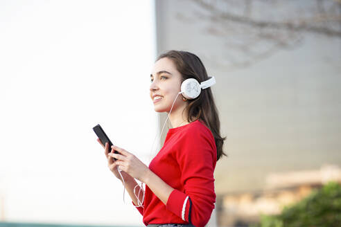 Happy woman listening music through headphones while holding mobile phone - JCCMF00252