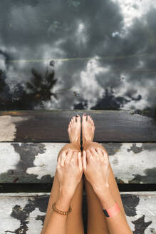 Bare legs of woman relaxing on steps of underground cenote - JMPF00748
