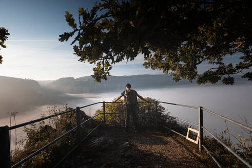 Male explorer with backpack admiring view of Danube Valley at Beuron, Swabian Alb, Germany - FDF00310
