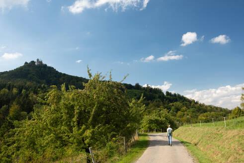 Woman walking on road toward Burg Hohenzollern at Swabian Alb, Germany - FDF00319