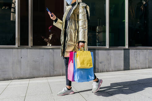 Young woman with protective face mask carrying shopping bags while using mobile phone walking on footpath - MARF00038