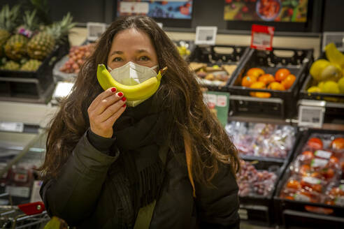 Mature woman in protective face mask showing banana while shopping in supermarket - NGF00734
