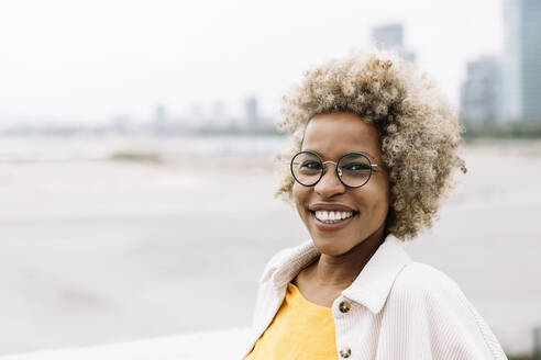 Woman wearing eyeglasses smiling while standing outdoors - XLGF00904