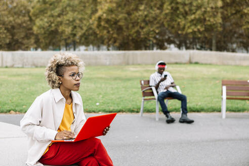 Woman using laptop while sitting bench with friend in background on bench - XLGF00913