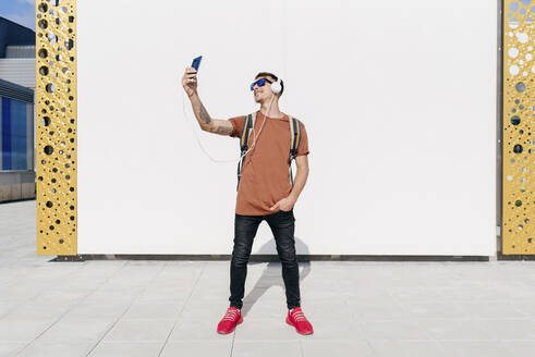 Smiling man wearing headphones taking selfie through mobile phone while standing with hands in pockets against wall - MARF00049