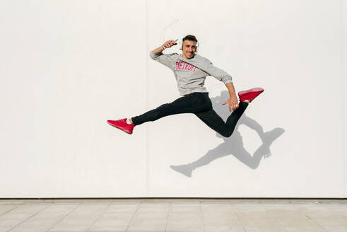 Carefree man wearing headphones holding smart phone while jumping against wall - MARF00055