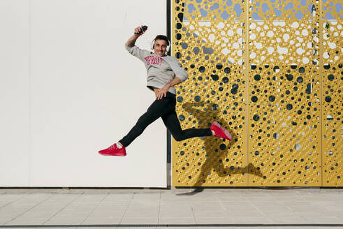 Carefree man with headphones and mobile phone jumping against wall - MARF00058