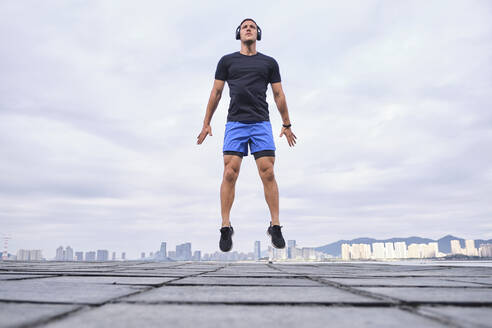 Ground level of energetic male runner warming up body and jumping on street during cardio training while looking away - ADSF19256