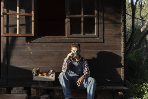 Male farmer with vegetable crate having coffee against wooden house on sunny day - JPTF00619