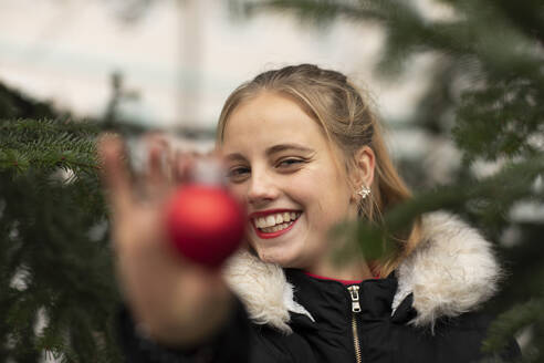 Happy young woman showing Christmas ornament during holidays - SGF02721