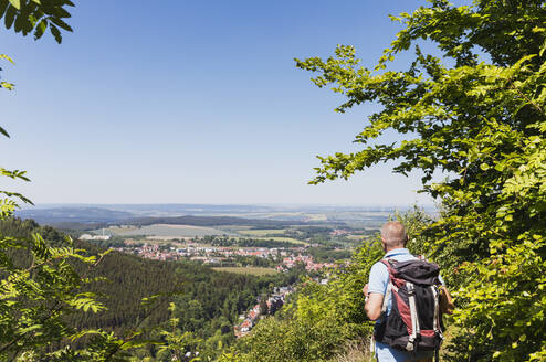 Germany, Thuringia, Bad Tabarz, Senior hiker admiring view of town in Thuringian Forest during spring - GWF06799