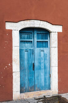 Exterior of old building with closed blue doors - JMPF00752