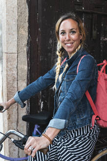 Smiling female tourist sitting on bicycle with backpack - JMPF00755
