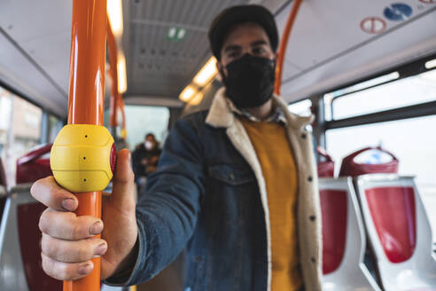 Businessman wearing protective face mask holding pole while commuting in bus - JAQF00047