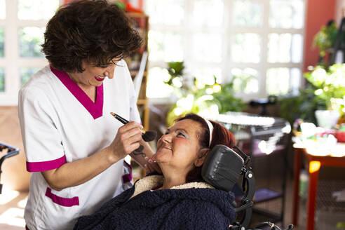 Smiling female nurse doing make-up of disabled woman in nursing home - LJF01937