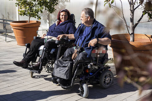 Disabled woman and man holding hands while sitting on wheelchair during sunny day - LJF02000