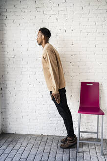 Man leaning by chair against white brick wall at home - RCPF00495