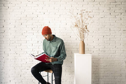 Man in knit hat reading book by dried plant vase against white brick wall - RCPF00507