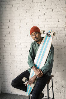 Confident man holding skateboard while sitting on stool against white brick wall - RCPF00510