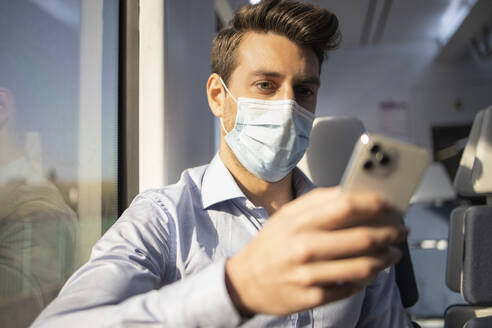 Mid adult businessman with face mask using smart phone while traveling by train during COVID-19 - IFRF00218