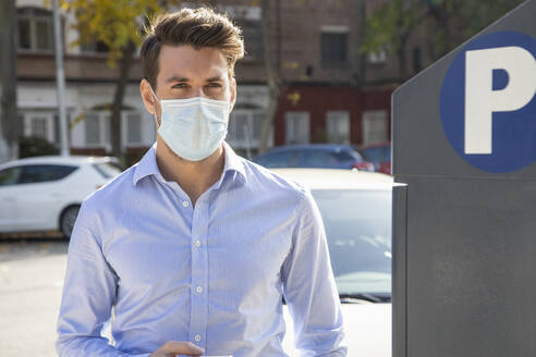 Businessman wearing face mask looking away while standing by parking meter in city - IFRF00221