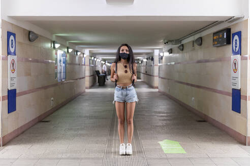 Woman with protective face mask standing at station underground passage - WPEF03836