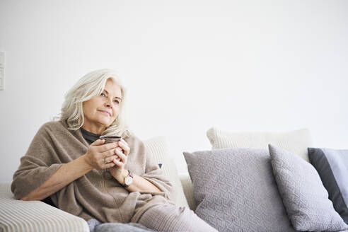 Thoughtful retired woman holding coffee cup while sitting on sofa against white wall at apartment - JAHF00032