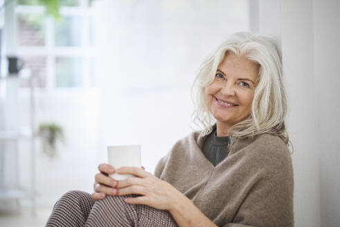 Happy senior woman holding coffee cup while sitting in living room at home - JAHF00041