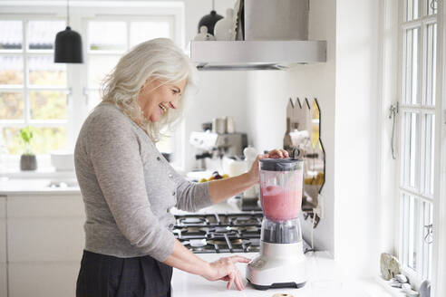 Happy retired woman preparing strawberry smoothie in processor at kitchen counter - JAHF00056