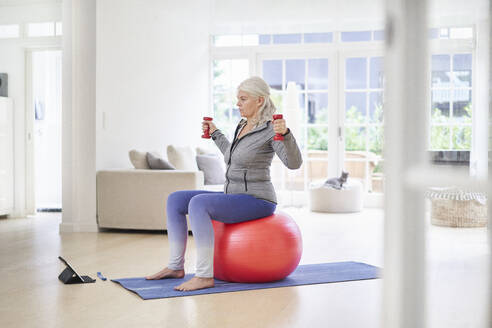 Senior woman exercising while learning from online tutorial through digital tablet at home - JAHF00062