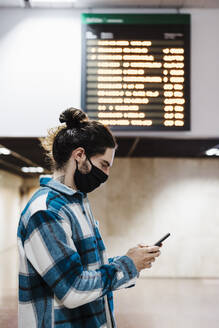 Man wearing protective face mask using mobile phone while standing at subway station - EBBF01895