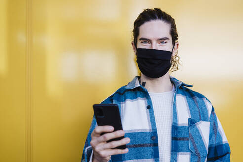 Young man with protective face mask and mobile phone staring while standing against yellow wall - EBBF01901