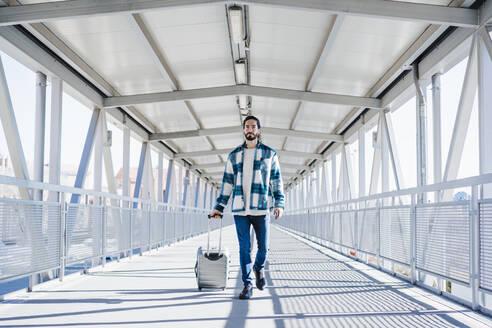Young man walking with luggage on bridge - EBBF01907