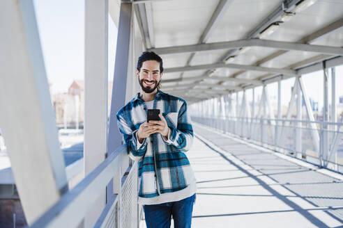 Smiling man using mobile phone while standing on bridge - EBBF01910