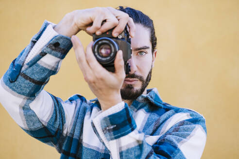 Young man photographing through camera while standing against yellow wall - EBBF01916