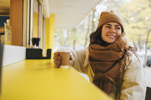 Smiling young woman with disposable coffee cup looking away at street cafe during winter - OYF00297