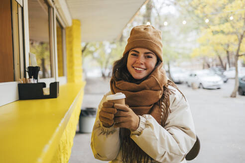 Happy woman at street cafe with disposable coffee cup during autumn - OYF00300