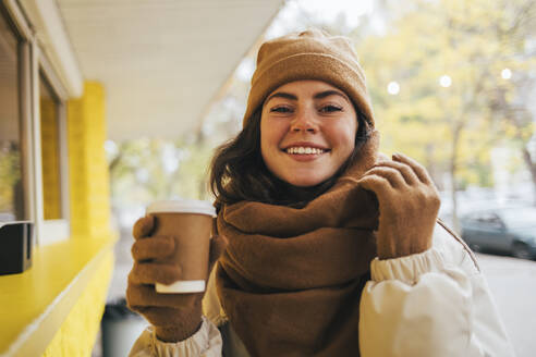 Smiling woman having coffee at street cafe during autumn - OYF00303