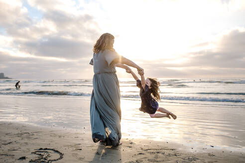 Mom swinging young daughter by the arms on the beach at sunset - CAVF91413