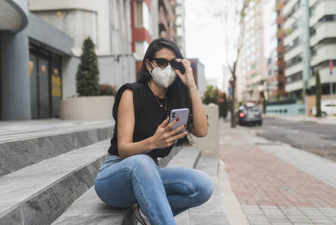 Woman with protective face mask using smart phone while sitting on steps in city - DSIF00254
