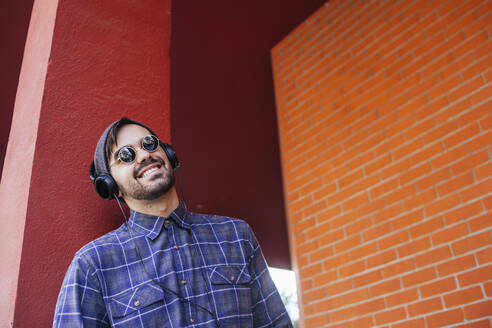 Smiling fashionable young man listening music through headphones against column - MGRF00097
