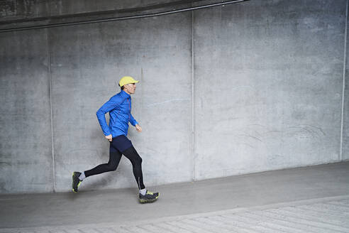 Mature man jogging in parking garage of residential building - JAHF00072